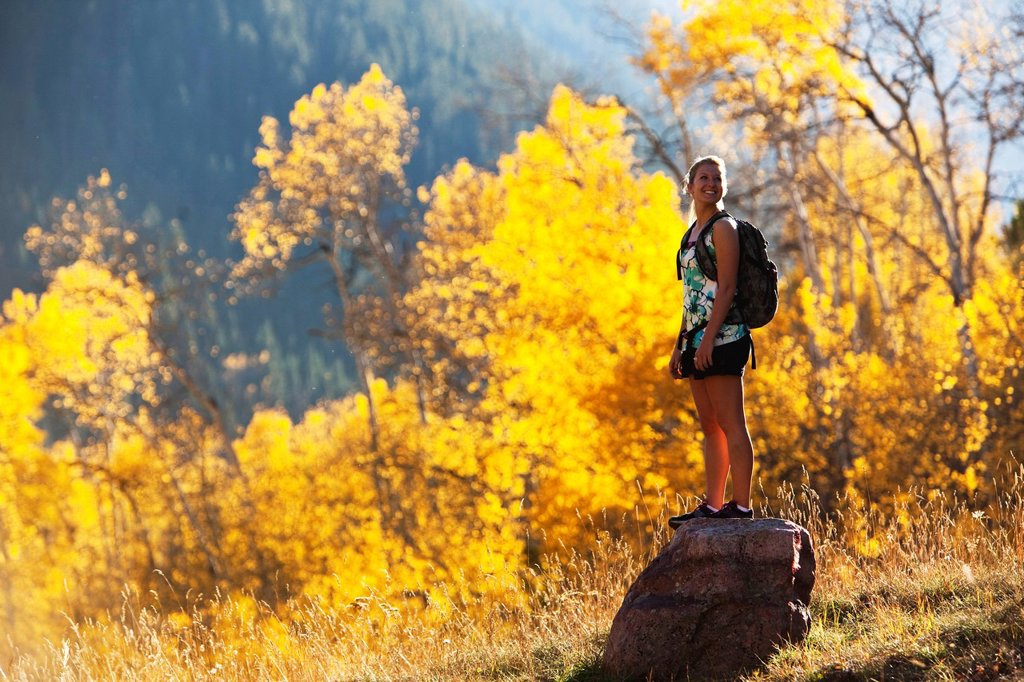 Stock Photo: 1778R-24940 A young woman hiking stops and enjoys the beauty of the golden fall colors.