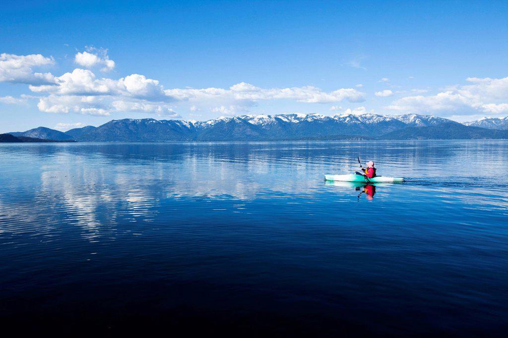 An adventurous women kayaking across a huge calm lake in Idaho. : Stock Photo