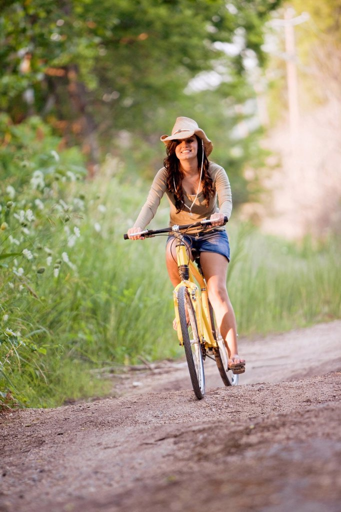 Stock Photo: 1778R-25857 a young woman rides a yellow bike down a dirt road.