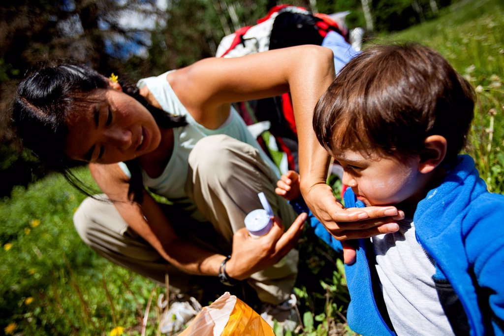 a mother applies sunscreen to her son as they sit in a grassy meadow, with their backpacks behind them, on the Williams Creek Trail trail number 587 during the beginning of their family backpacking trip. : Stock Photo