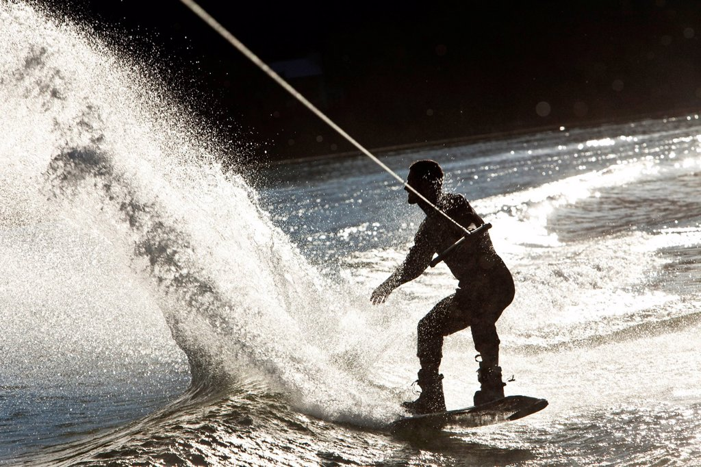 Stock Photo: 1778R-26365 A professional wakeboarder carves and slashes on a lake at sunset in Idaho.