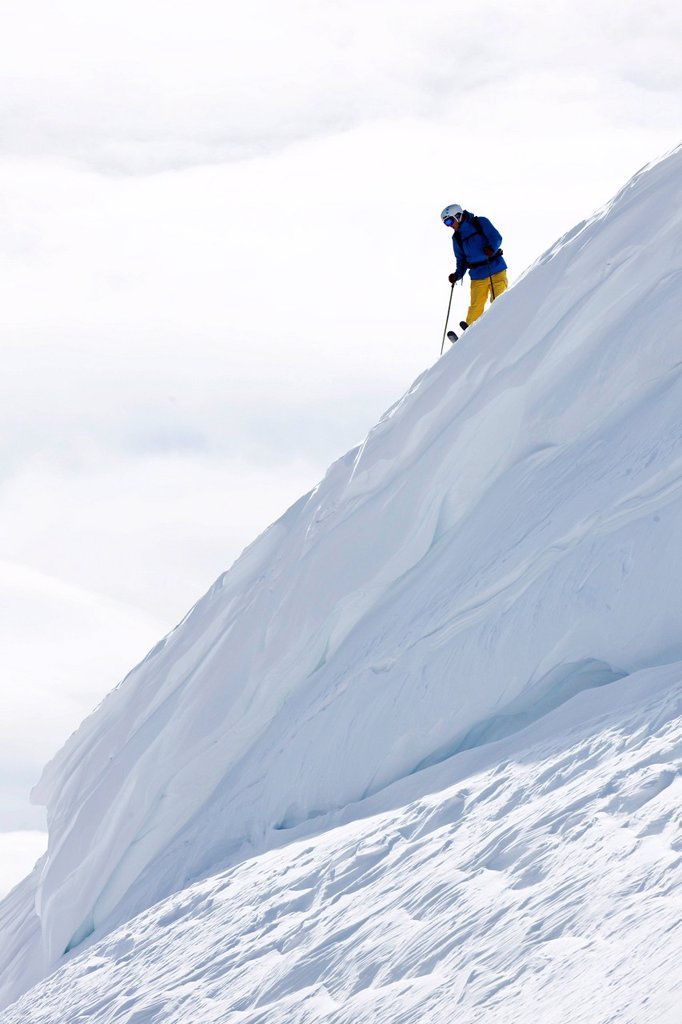 Stock Photo: 1778R-26591 A skier scouts his line standing on top of a huge cornice in Colorado.