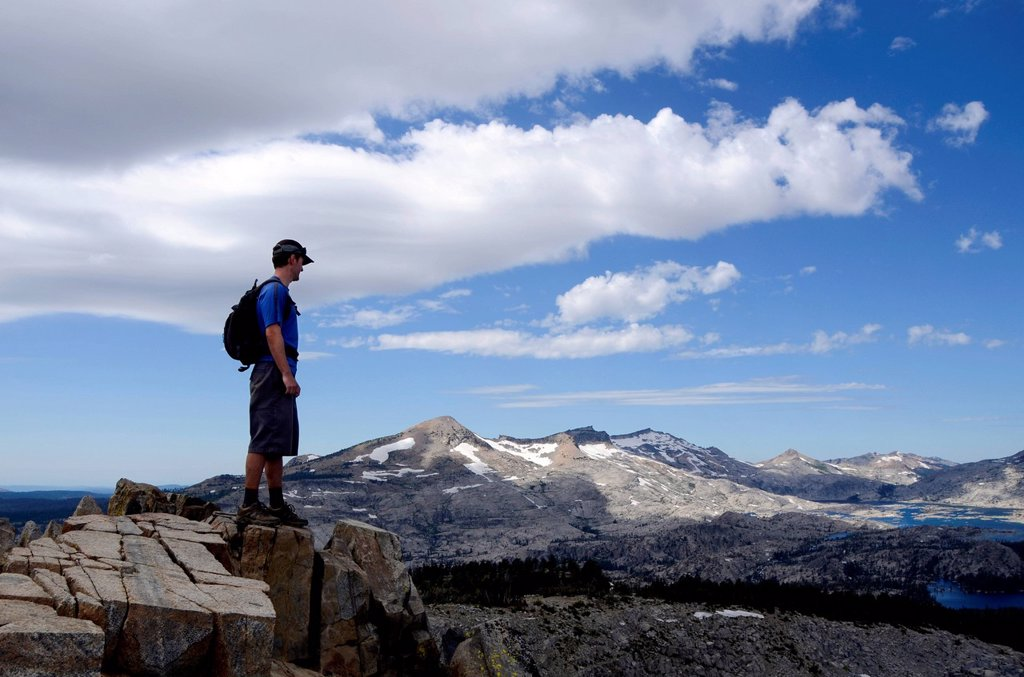 A male hiker stands on the summit of Mount Ralston looking over Pyramid Peak and Desolation Wilderness in the summer, CA. : Stock Photo