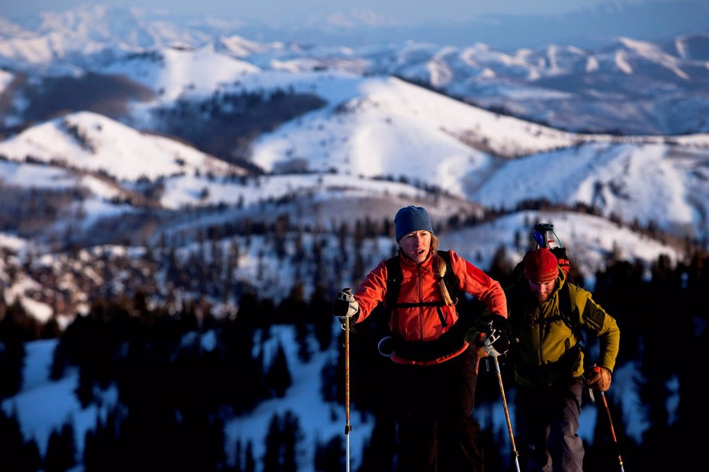 Man and woman backcountry skiers reaching their summit in beautiful sunrise light. : Stock Photo