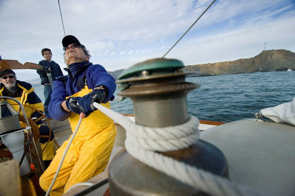 A man trims the sails on his yacht. : Stock Photo