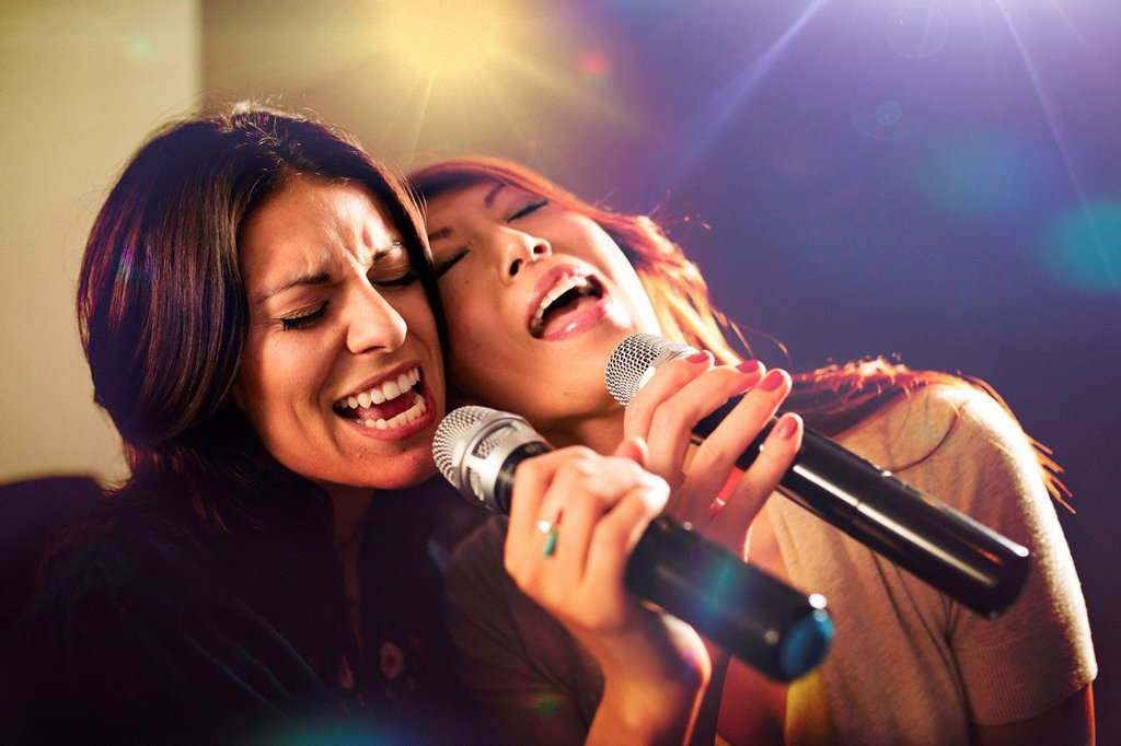 Stock Photo: 1778R-30265 Two women singing karaoke.
