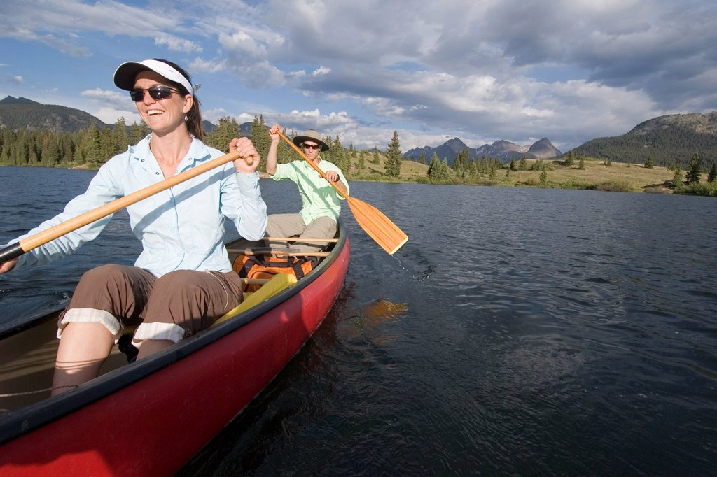 Woman and man in red canoe on lake. : Stock Photo
