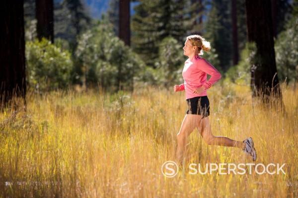 A woman running through tall grass. : Stock Photo