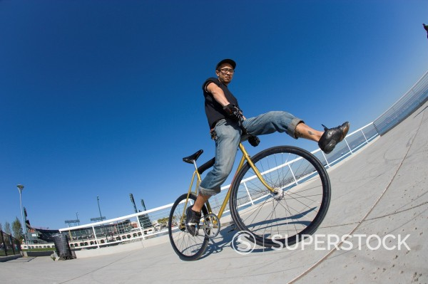 Stock Photo: 1778R-3329 A man does tricks on fixed gear bike.