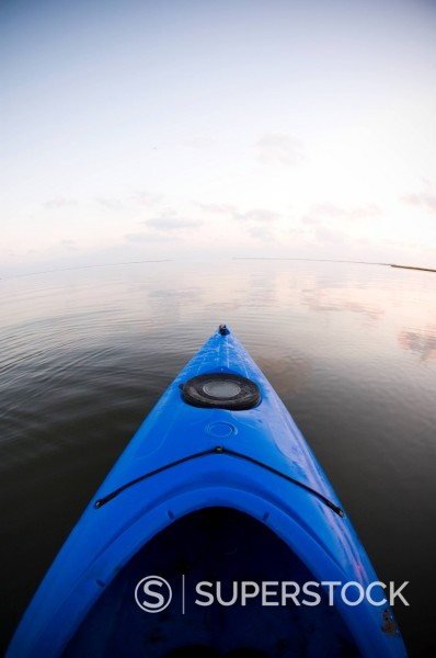 Stock Photo: 1778R-3517 Dawn breaks over a bayou in a kayak.