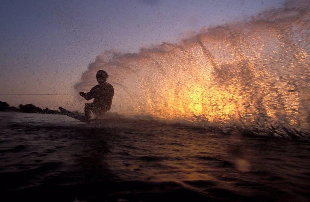 Stock Photo: 1778R-3616 Water skier riding low to create spray.