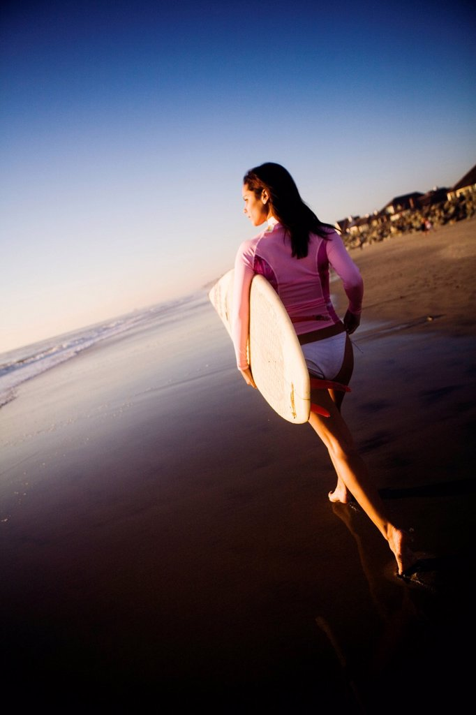 Young woman with surfboard on beach. : Stock Photo