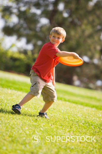 A smiling young boy tosses a throwing disc or Frisbee on a sunny summer afternoon in a grassy park in California. : Stock Photo