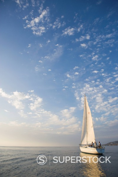 A sailing yacht out on the open water on a clear evening at sunset near San Diego, California. : Stock Photo