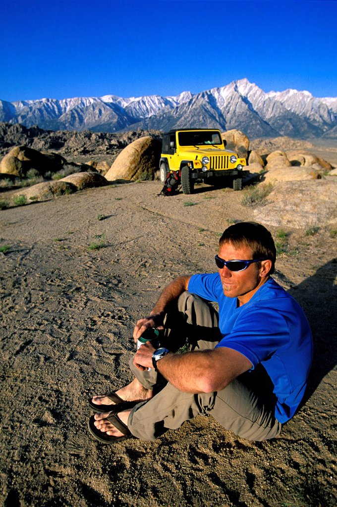 Stock Photo: 1778R-4376 Man with sunglasses sitting in the desert next to his 4_wheel drive vehicle in front of mountains.