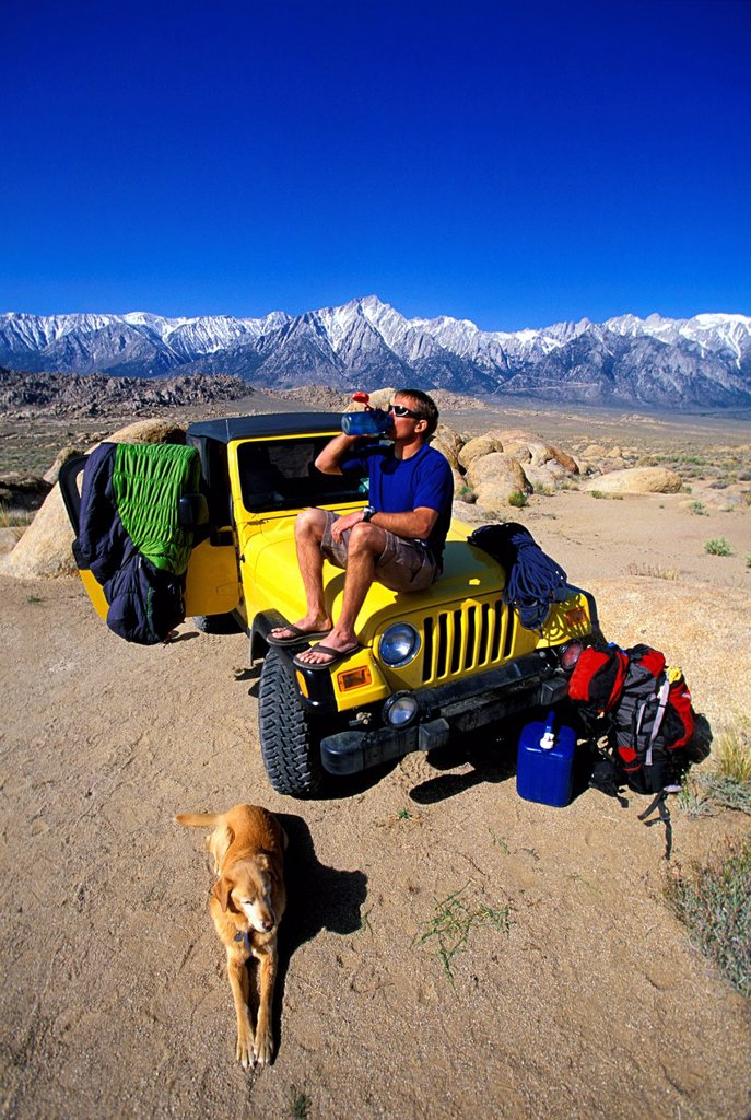 Stock Photo: 1778R-4377 Man sitting on a 4_wheel drive vehicle in the desert with his dog taking a drink from a water bottle.
