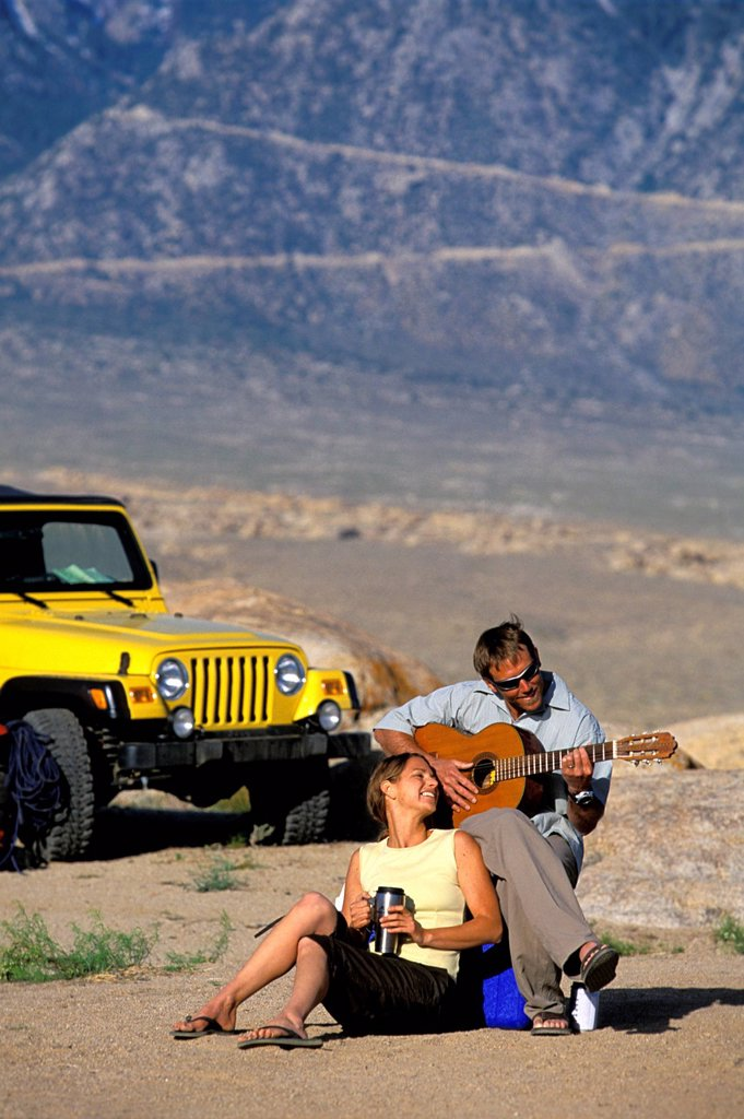 Stock Photo: 1778R-4380 Man and woman sitting next to a 4_wheel drive vehicle in the desert playing a guitar.