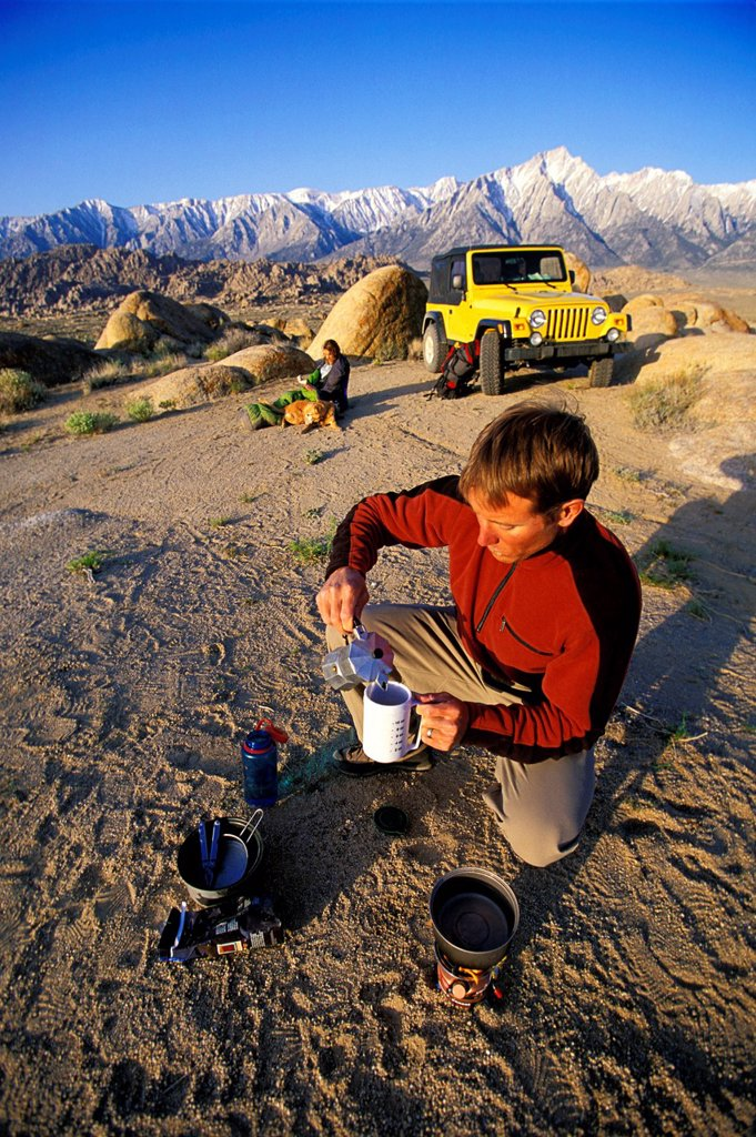 Stock Photo: 1778R-4382 Man making coffee on a camp stove in the desert with a woman,4_wheel vehicle and mountains in the background.