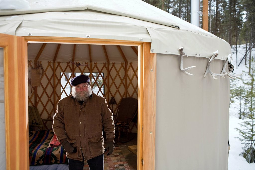Stock Photo: 1778R-4441 Bearded man with hat in sparse yurt, Whitefish, Montana.