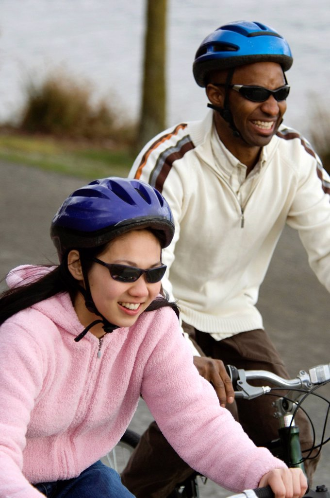 Stock Photo: 1778R-4508 A young couple in helmets ride bikes on a path near the ocean.