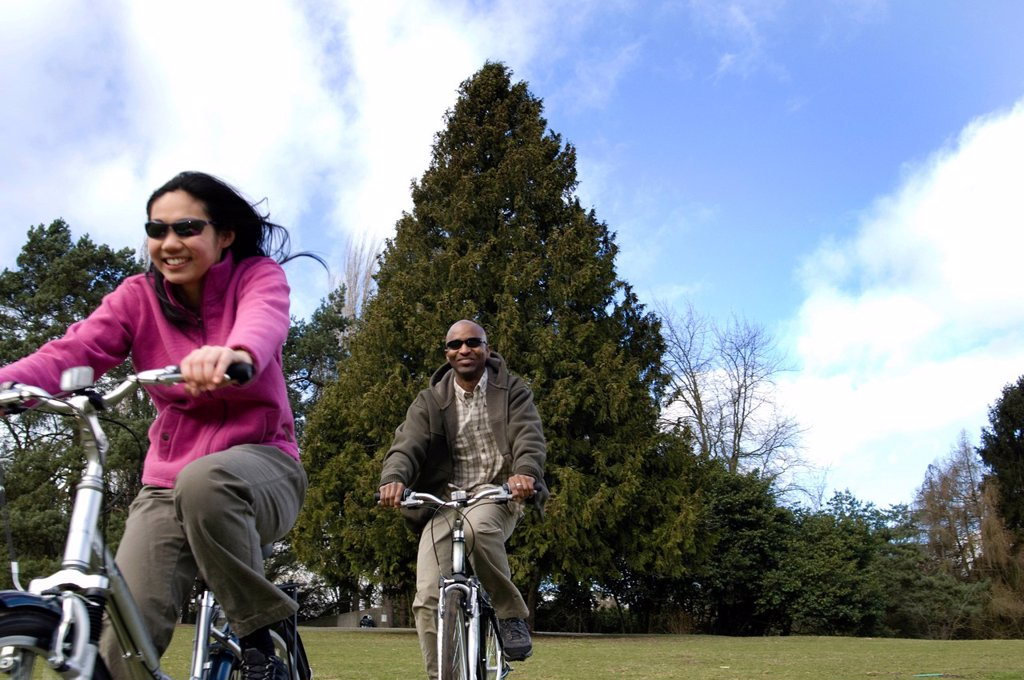 A young couple ride bikes on a sunny day. : Stock Photo