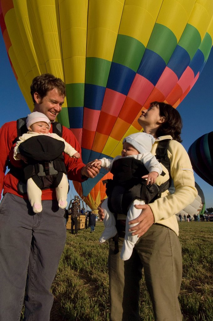 A family with twin babies watches hot air balloons launch during a festival. : Stock Photo
