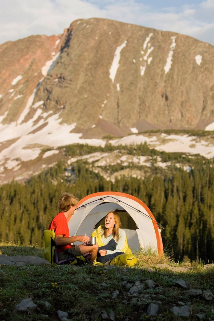 Stock Photo: 1778R-5220 A young couple laughing in tent below a peak, San Juan National Forest, Colorado.