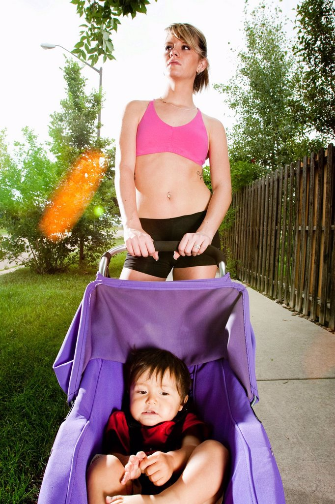 An edgy_looking, athletic young woman with tattoos stops during a run on a suburban sidewalk with a baby in a jogging stroller. : Stock Photo