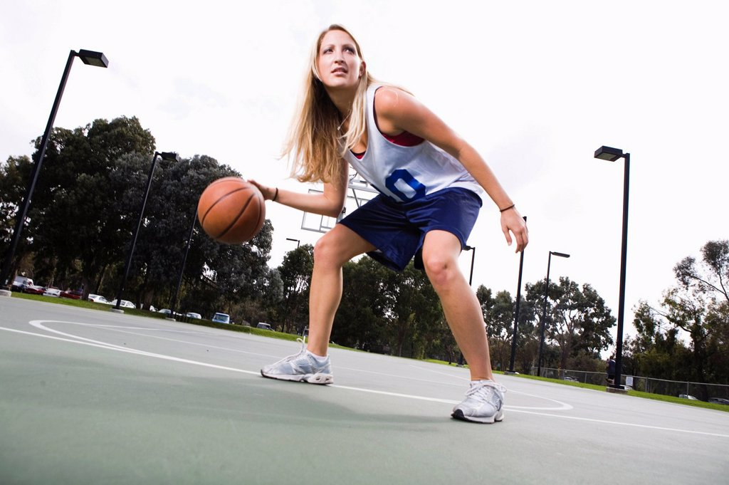 Action shot of a woman playing basketball. : Stock Photo