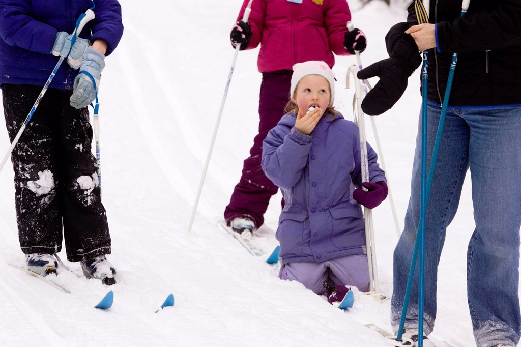 A young girl eat some snow, while Cross Country Skiing in Dayton, Maine. : Stock Photo