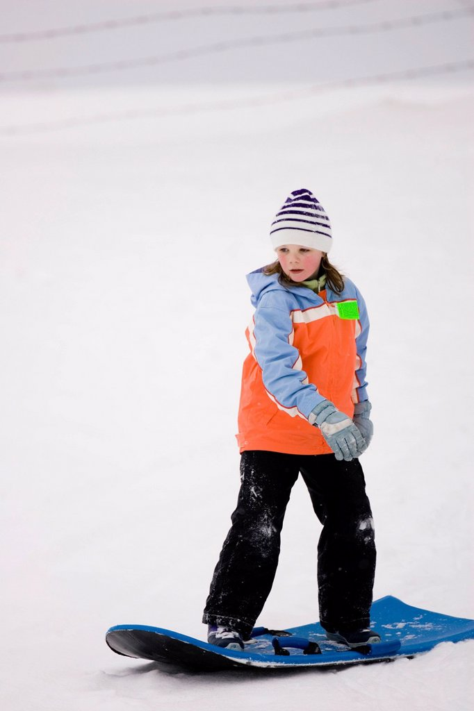 A young girl surfs on a snow sled in Dayton, Maine. : Stock Photo
