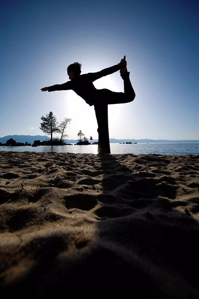 Silhouette of a woman doing yoga on a beach by a lake in the mountains. : Stock Photo