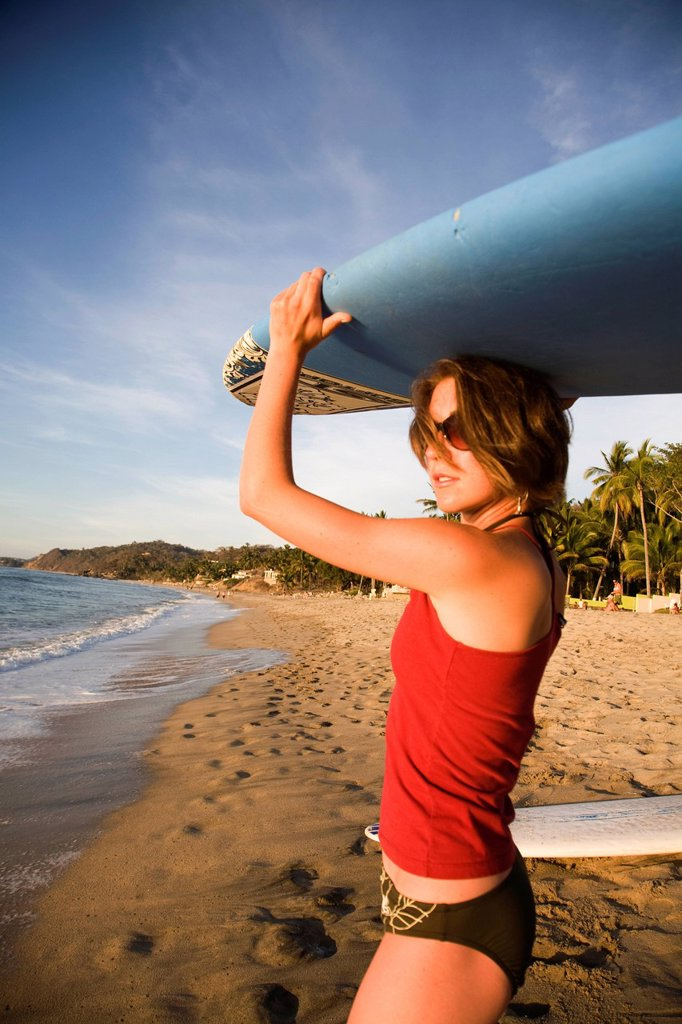 A girl wearing a red top and bikini bottoms holds a surfboard over her head on a remote beach in Sayulita, Mexico. : Stock Photo