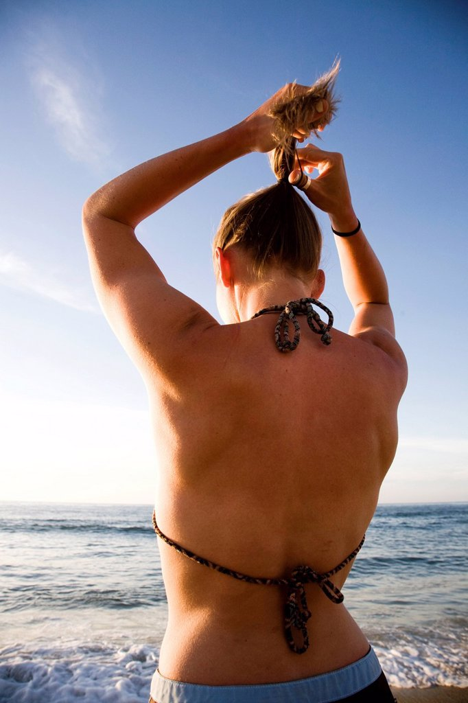 A young woman fixes her pony tail on a beach in Sayulita, Mexico. : Stock Photo