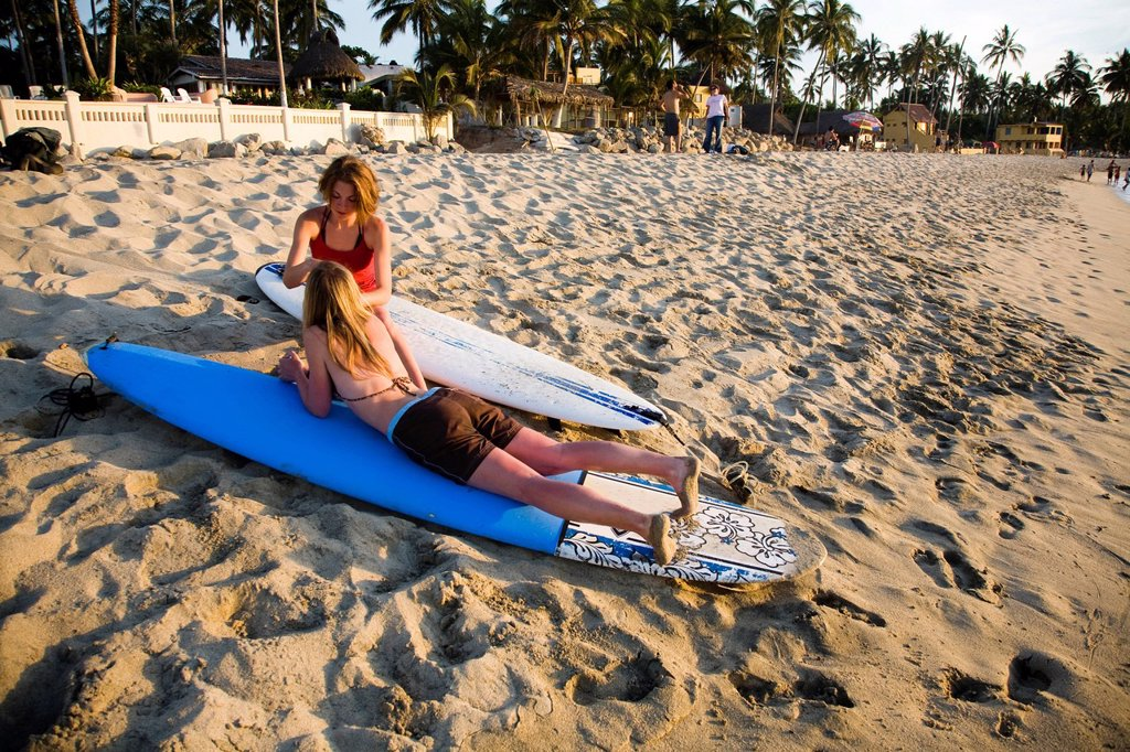 Two young girls sit on their surfboards after surfing near a remote beach in Sayulita, Mexico. : Stock Photo