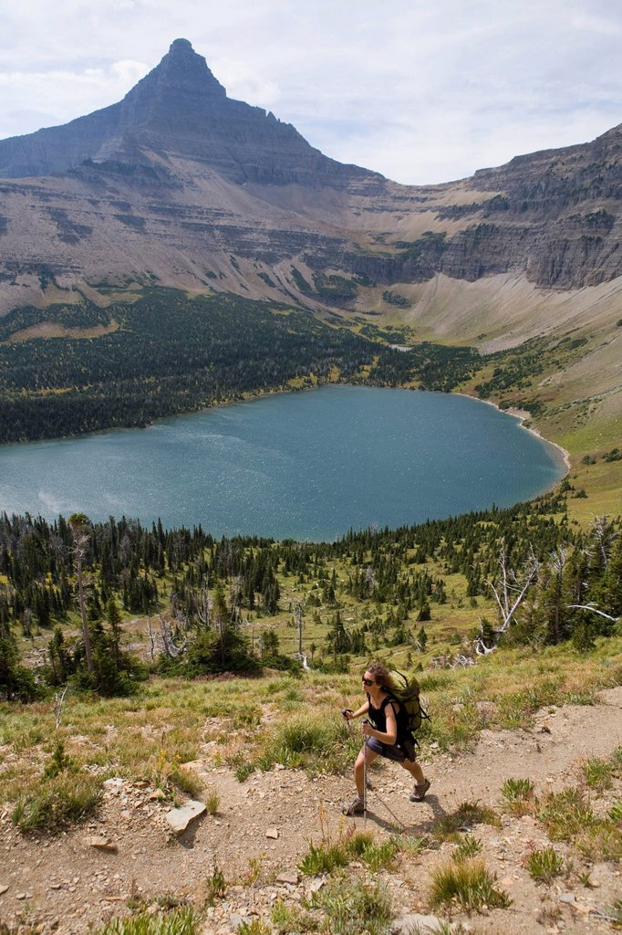 Solo female hiking out of mountains on a trail with a lake deep in Glacier National Park. : Stock Photo