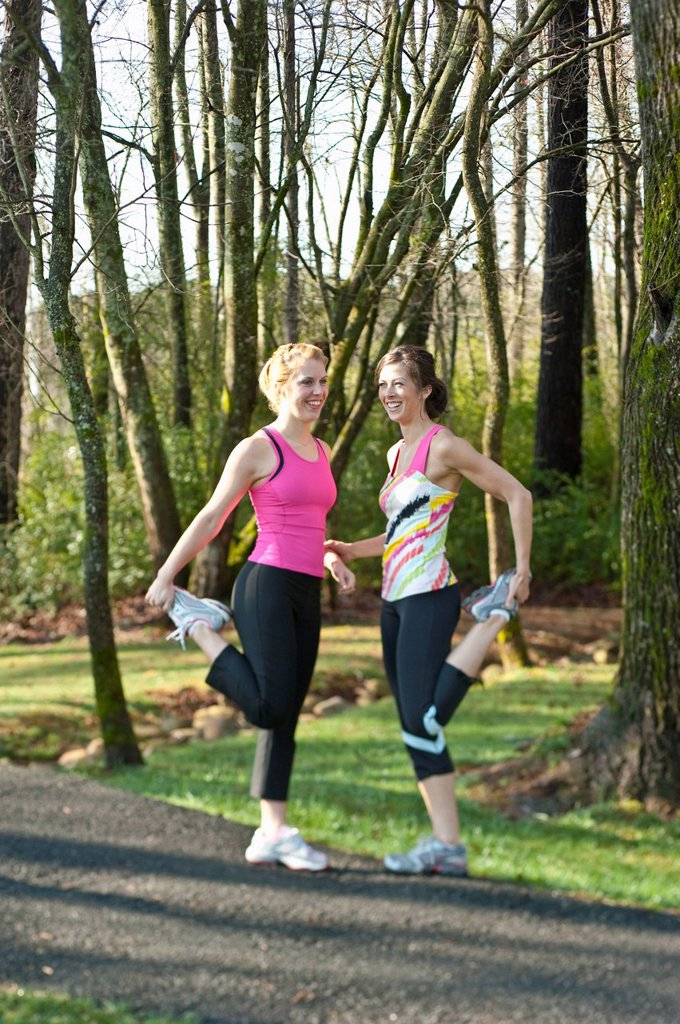 Two women in their mid_20´s stretching leg muscles outdoors. : Stock Photo