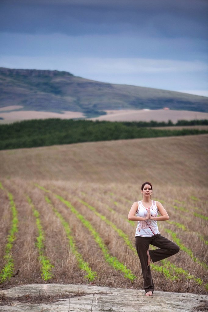 Stock Photo: 1778R-7394 A woman practices yoga in a field under cloudy skies in Brazil.