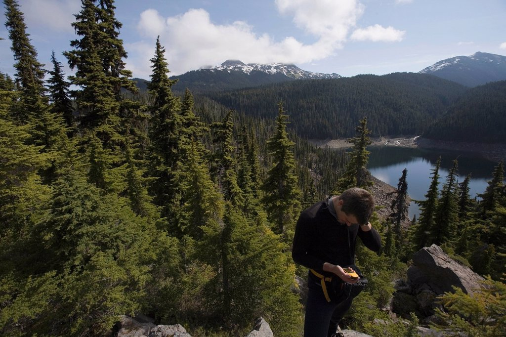 Stock Photo: 1778R-7477 A man checks his location on a GPS global positioning system near Squamish, British Columbia.