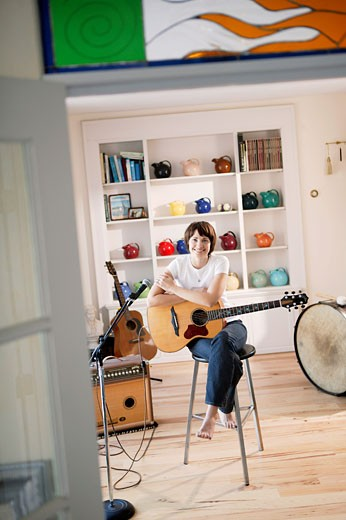 Young woman holding acoustic guitar with amplifier : Stock Photo