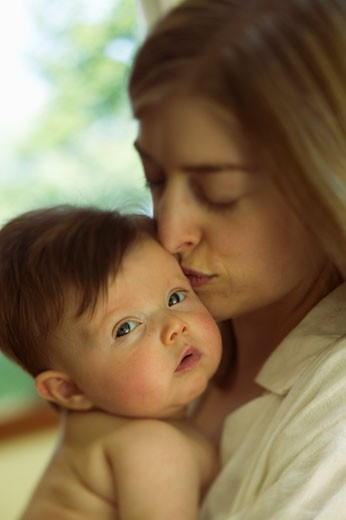Stock Photo: 1779R-11060 Mother kissing newborn