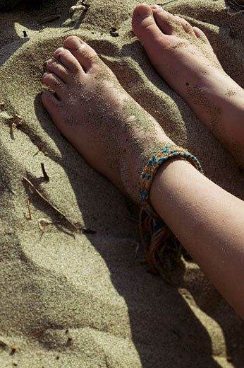 Young girl's feet in the sand : Stock Photo