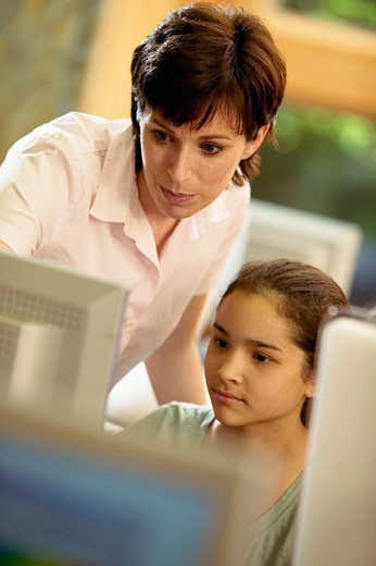 Teenage girl using computer with teacher : Stock Photo