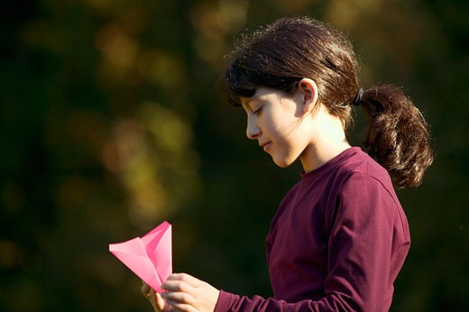 Stock Photo: 1779R-11120 Girl opening paper airplane