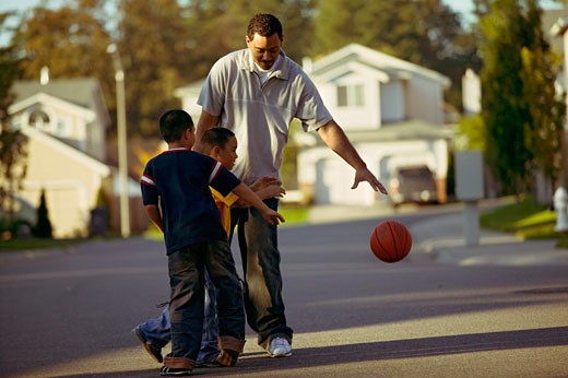 African father and sons playing basketball : Stock Photo