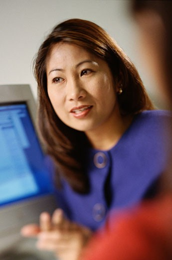 Asian woman sitting at office desk : Stock Photo