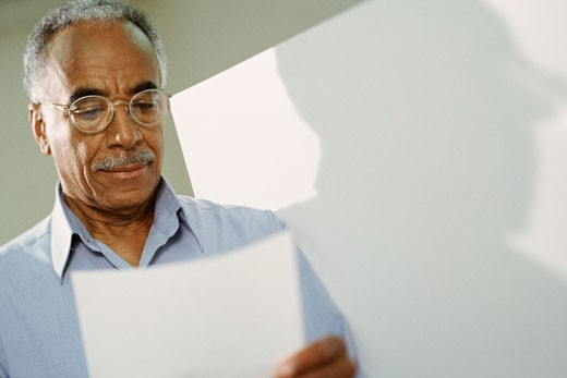 African man examining piece of paper : Stock Photo