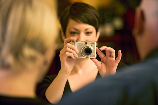 Woman taking a picture of couple : Stock Photo