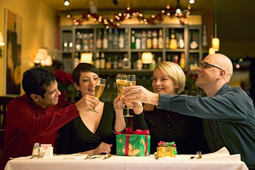 Couples toasting each other at dinner table : Stock Photo