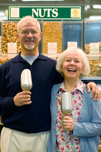 Stock Photo: 1779R-11653 Couple holding spades while they shop for nuts